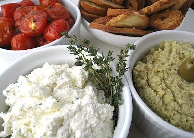 HERBED RICOTTA WITH ROASTED TOMATOES AND ARTICHOKE SPREAD AND CROSTINI